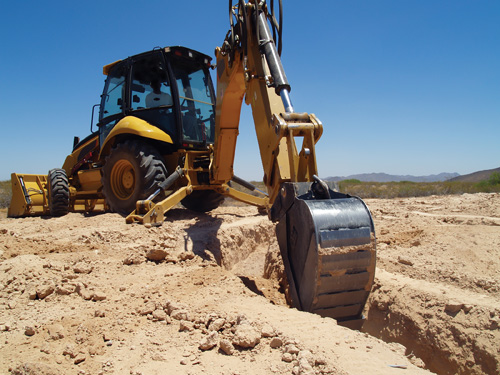 A construction Back Hoe digging the footings for a foundation.