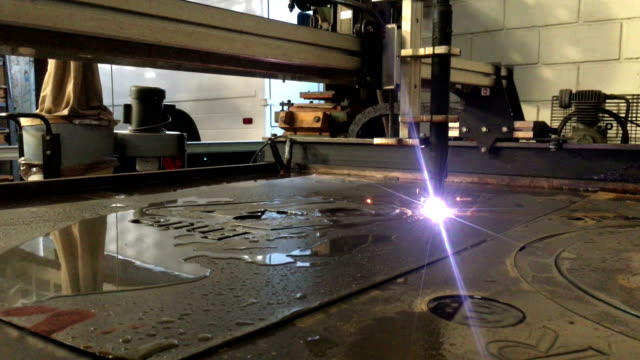 Plasma cutter seen from its mechanical arm roll during the process of cutting a steel sheet.